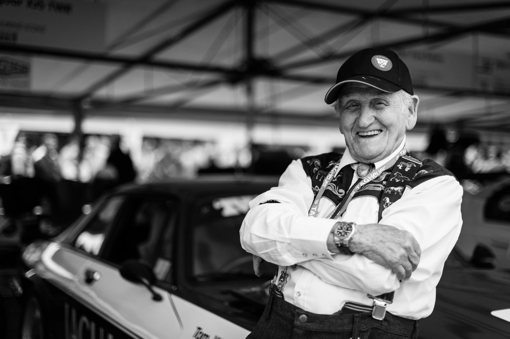 Sir Norman Dewis at Goodwood Festival of Speed leans on a Jaguar Car smiling