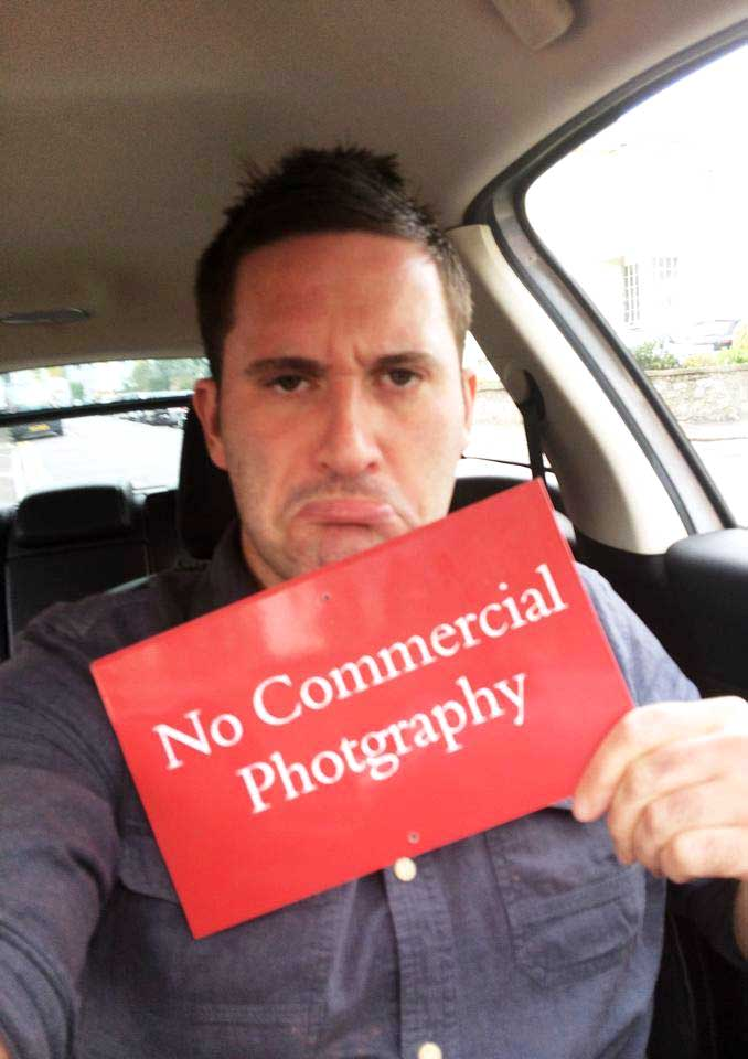 """Avant photographer Phil holding a sign that is mispelled saying: """"No commercial Photgraphy"""""""
