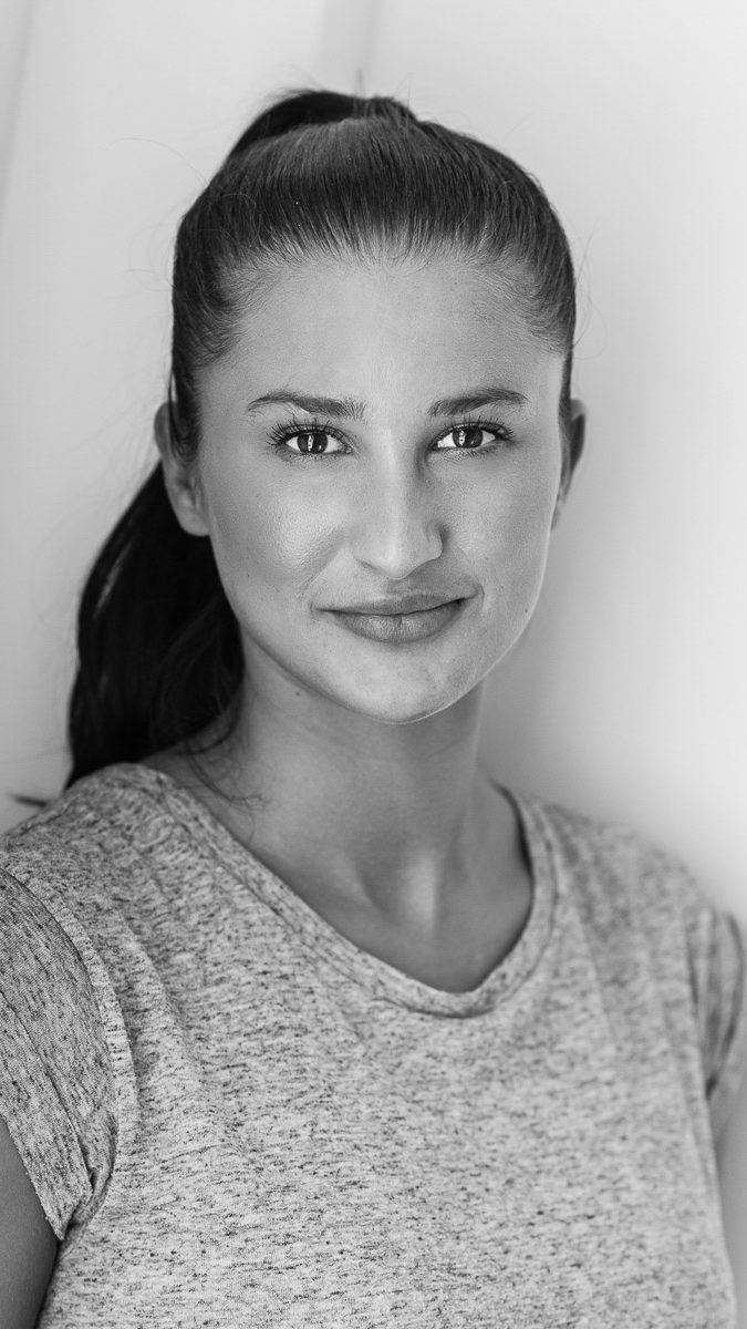 headshot photography Sussex - black and white headshot of female with hair up taken at Avant Commercial Eastbourne y Photographer Phil Burrowes Avant Commercial professional photography for your business - Avant Photographic -photographer Phil Burrowes - Commercial photography - visual content for social media & websites - tell the story of your business