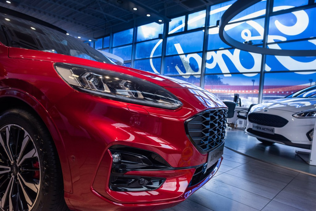 Car sales franchise photography of red Ford Kuga front